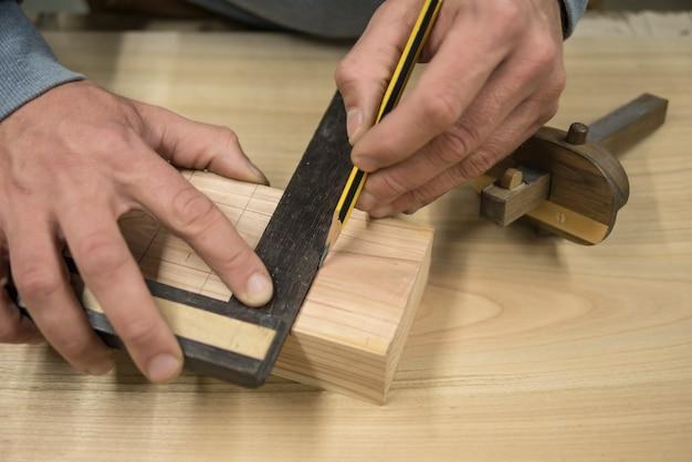 Ein schreiner mit einem bleistift und einem quadrat markiert das werkstück