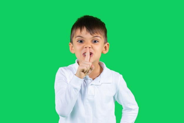 Ein schüler in einem weißen hemd zeigt leise seinen zeigefinger und schaut in die kamera grün