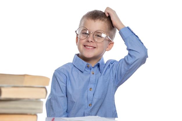 Ein schuljunge mit brille sitzt an einem tisch und lacht. isoliert weiß