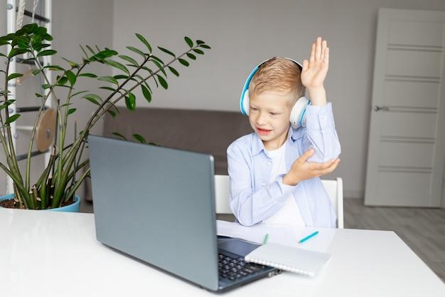 Ein schuljunge mit kopfhörern hebt seine hand, um eine lektion während der fern-e-bildung zu hause zu beantworten. homeschooling. zurück zur schule