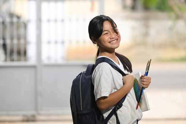 Ein schulmädchen hält eine malausrüstung in der hand und trägt eine schultasche, während es auf einen schulbus wartet.