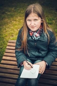 Ein schulmädchen im frühjahr, das auf einer hölzernen chaiselongue in einem waldgebiet sitzt, schreibt einen brief