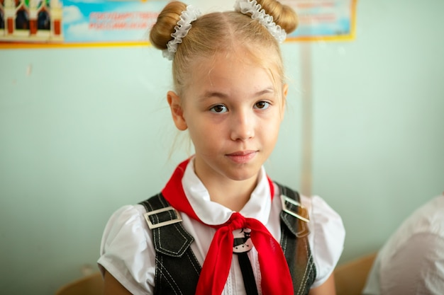 Ein schulmädchen in einer weißen bluse mit roter krawatte und einer schleife in der klasse. zurück zum schulkonzept.