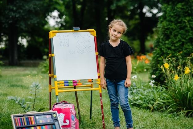 Ein schulmädchen schreibt unterricht an einer tafel und macht outdoor-training. zurück zur schule, lernen während der pandemie.
