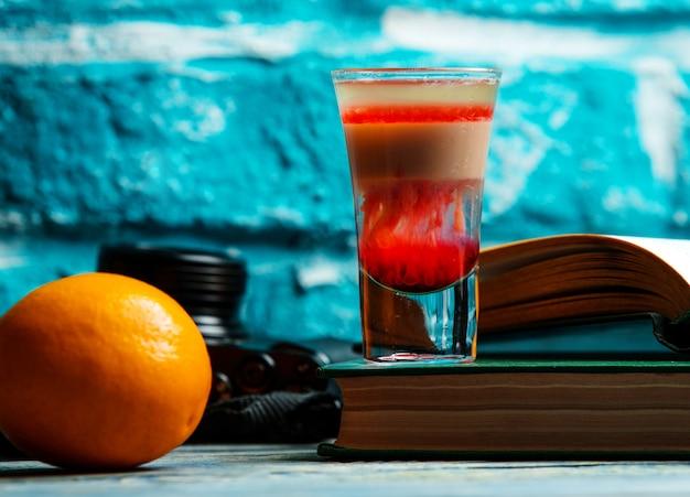 Ein schuss des roten cocktails und der orange