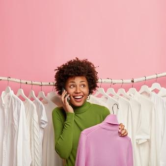 Ein schuss einer glücklichen afroamerikanerin wählt neue kleidung im ausstellungsraum aus, nimmt einen lila rollkragenpullover an den kleiderbügeln auf und steht über einem satz weißer kleidung an den kleiderbügeln