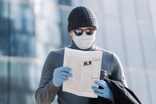 Ein schuss eines jungen mannes liest einen artikel über coronavirus-symptome, trägt eine medizinische schutzmaske und gummihandschuhe und posiert auf der straße mit kaffee. covid-19-schutzkonzept