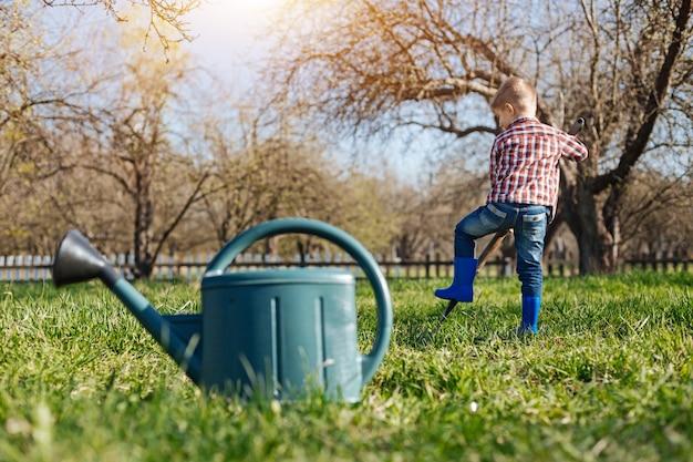 Ein schuss eines kindes, das hellblaue gummistiefel trägt, die ein loch in den boden graben und eine grüne gießkanne, die vorne steht