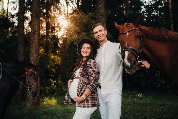 Ein schwangeres mädchen in einem hut und ein mann in weißer kleidung stehen neben pferden im wald in der natur