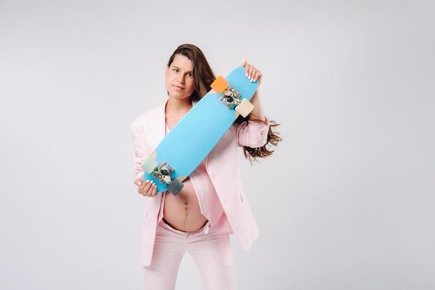 Ein schwangeres mädchen in einem rosa anzug mit einem skateboard in den händen steht auf einem grauen hintergrund.