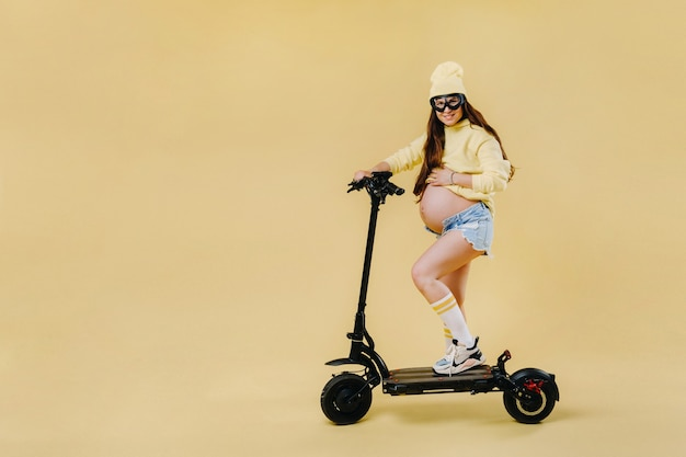 Ein schwangeres mädchen in gelber kleidung auf einem elektroroller auf einem isolierten gelben hintergrund