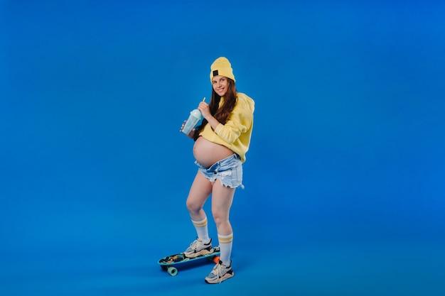 Ein schwangeres mädchen in gelber kleidung mit einem glas saft fährt ein skateboard auf blauem hintergrund.