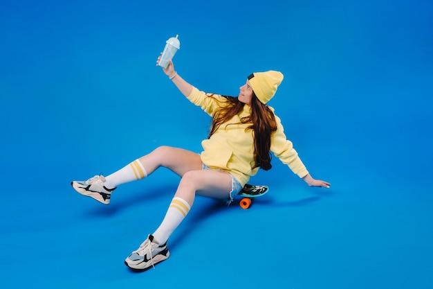 Ein schwangeres mädchen in gelber kleidung mit einem glas saft sitzt auf einem skateboard auf blauem grund.