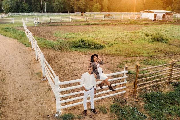 Ein schwangeres mädchen mit hut und ihr mann in weißer kleidung stehen bei sonnenuntergang neben einem pferdepferch. ein stilvolles paar wartet auf ein kind in der natur.