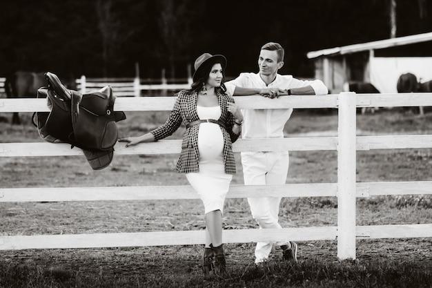 Ein schwangeres mädchen mit hut und ihr mann in weißer kleidung stehen neben dem pferdekorral. ein stilvolles paar, das auf ein kind wartet, steht auf der straße in der nähe des pferdekorrals. schwarz-weiß foto.