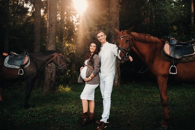 Ein schwangeres mädchen mit hut und ihr mann in weißer kleidung stehen neben pferden im wald in der natur. stilvolle schwangere frau mit einem mann mit pferden. familie.