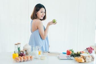Ein schwangeres schönes Mädchen Asiens hält den grünen Apfel