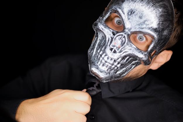 Ein schwarz gekleideter mann steht mit skelettmaske vor der kamera und richtet seine krawatte zurecht