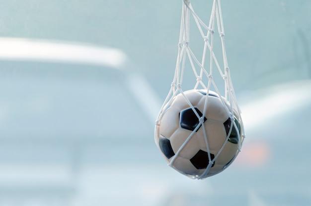 Ein schwarz-weißer fußball wiegt im netz als andenken