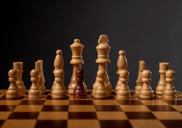 Ein schwarzer bauer einzigartig und anders in der gruppe anderer schachfiguren. konzept der vielfalt.