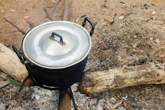 Ein schwarzer edelstahltopf wird lange auf dem herd platziert und wird nun zum gurten verwendet