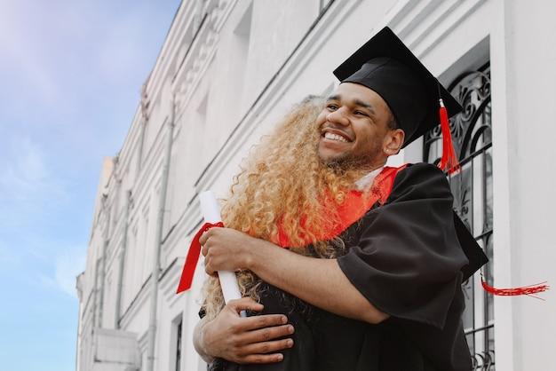 Ein schwarzer glücklicher absolvent im kleid und ein schwarzer doktorhut mit roter quaste lächeln glücklich. er hält ein diplom in der hand und umarmt ein klassenkamerad