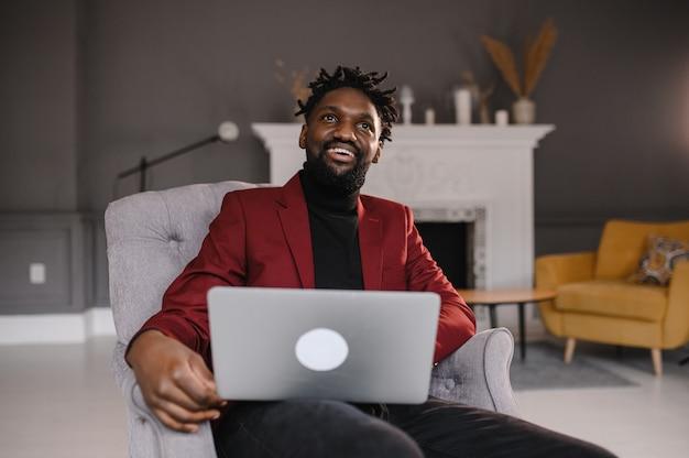 Ein schwarzer mann arbeitet an einer laptop-nahaufnahme seiner gesichtsvideokonferenzen