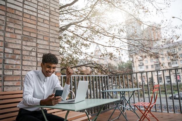 Ein schwarzer mann sitzt auf einer sommerterrasse oder veranda in der nähe eines cafés. der typ arbeitet an einem laptop. blick auf das frühjahrsgeschäft in der innenstadt.