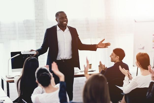 Ein schwarzer mann spricht mit angestellten des amtes auf einem seminar.