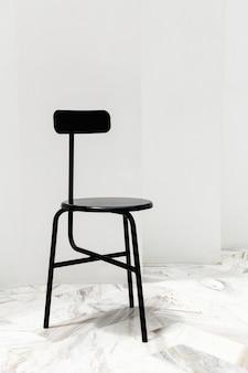 Ein schwarzer moderner stuhl auf einem weißen marmorboden