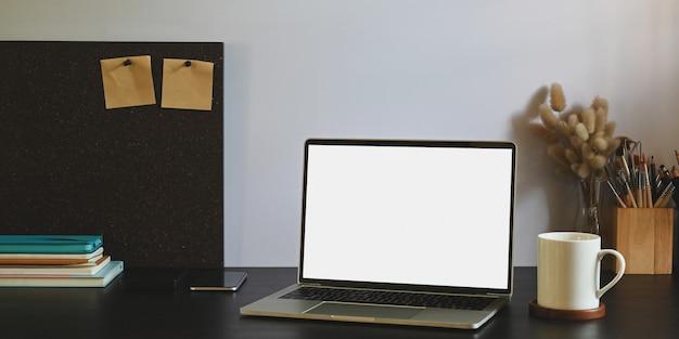 Ein schwarzer schreibtisch ist von einem computer-laptop und bürogeräten umgeben