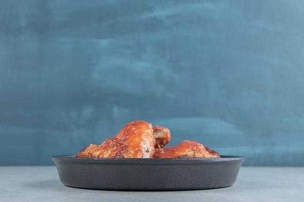 Ein schwarzer teller mit gebratenem fleisch in tomatensauce.