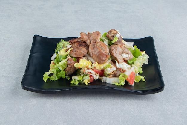 Ein schwarzer teller mit gebratenem hühnerfleisch und gemüsesalat.