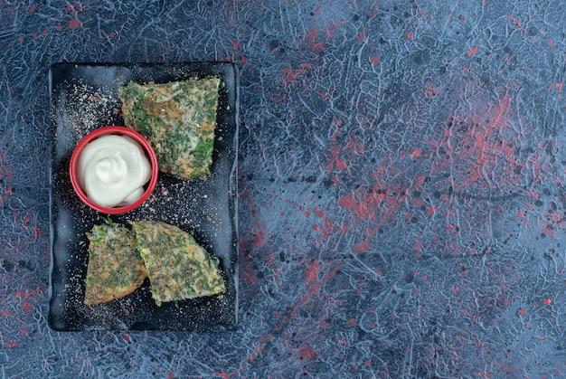 Ein schwarzer teller mit gebratenem omelett mit kräutern und sauerrahm.