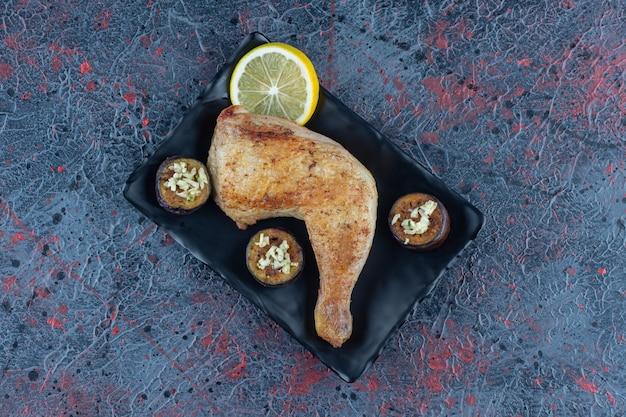 Ein schwarzer teller mit gegrilltem hühnerbein mit gebratener aubergine.