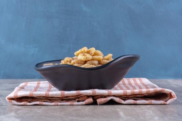 Ein schwarzer teller mit gesunden müsliringen zum frühstück auf tischdecke.
