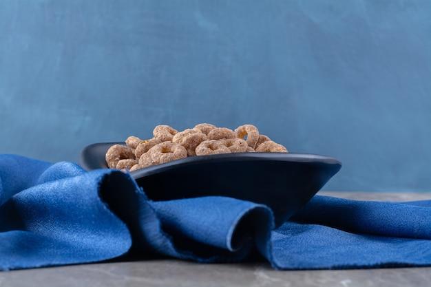 Ein schwarzer teller mit gesunden schokoladen-müsliringen zum frühstück.