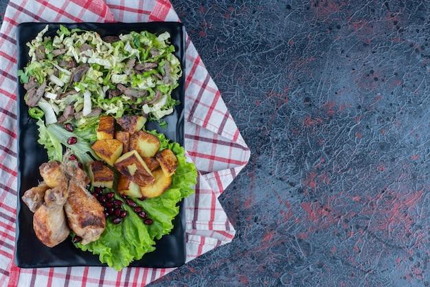 Ein schwarzer teller mit hühnerfleisch mit gemüsesalat.