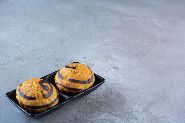 Ein schwarzer teller mit zwei süßen kuchen mit schokoladensirup auf grauem hintergrund.