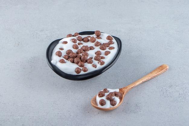Ein schwarzer tiefer teller milch mit schokoladengetreide und holzlöffel. foto in hoher qualität