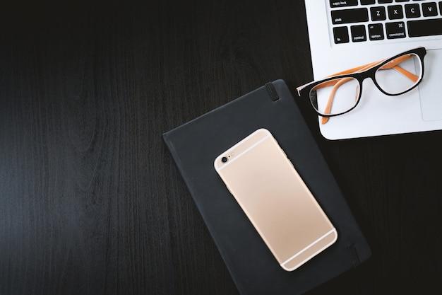 Ein schwarzer tisch mit laptop, smartphone und tagebuch