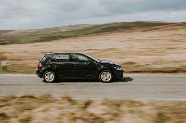 Ein schwarzes auto fährt auf der autobahn in wales, uk