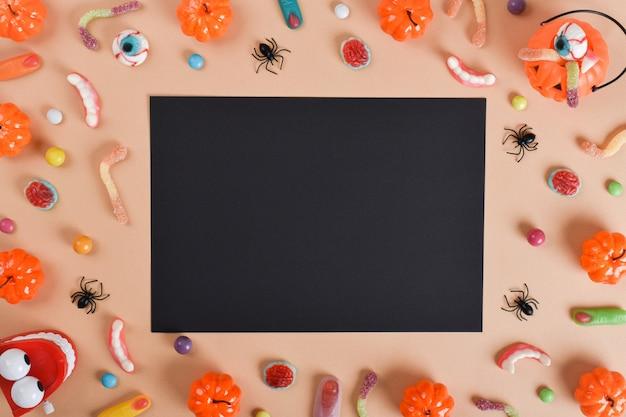 Ein schwarzes blatt neben verschiedenen süßigkeiten auf orangefarbenem hintergrund mit einem platz für text.