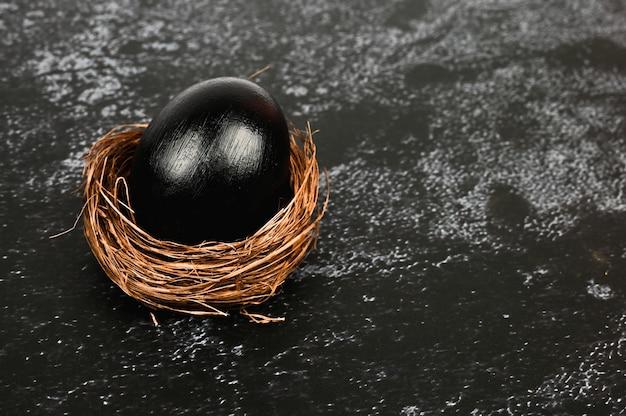 Ein schwarzes ei im nest auf dunkler oberfläche