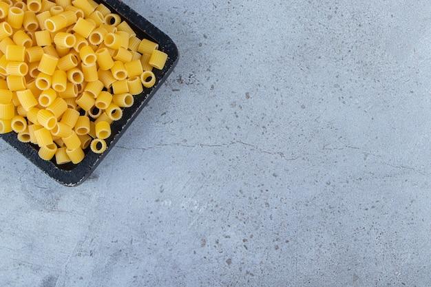 Ein schwarzes holzbrett aus rohen, trockenen ditali rigati-nudeln.