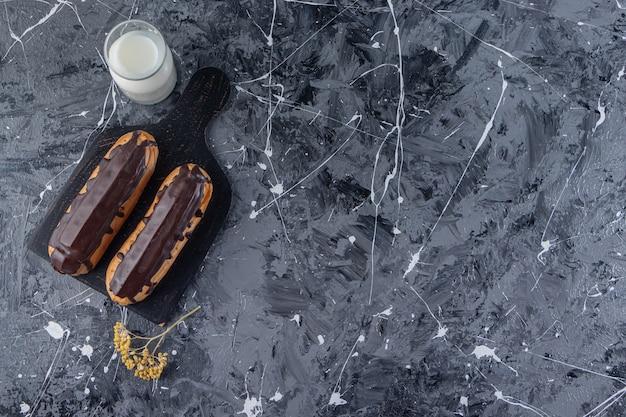 Ein schwarzes holzbrett aus zwei leckeren schokoladen-eclairs mit einem glas milchkrug.