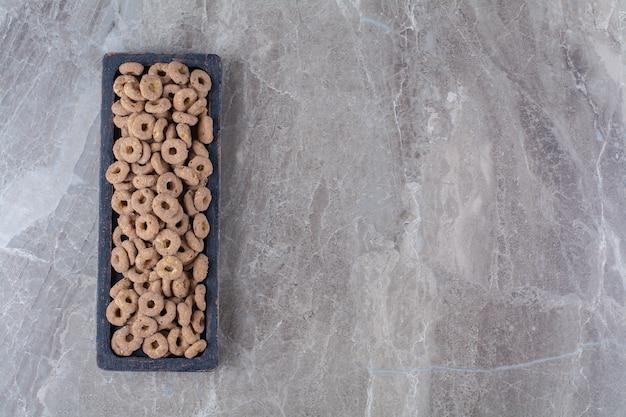 Ein schwarzes holzbrett mit gesunden schokoladen-müsliringen zum frühstück.