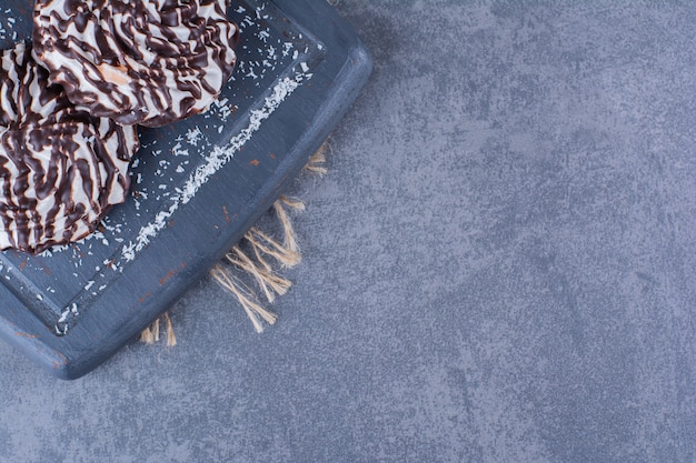 Ein schwarzes holzbrett mit süßen keksen auf einem sack.