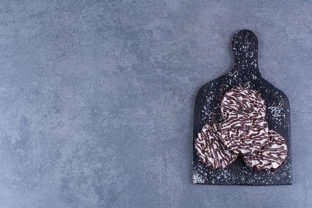 Ein schwarzes holzbrett mit süßen keksen auf einem stein.