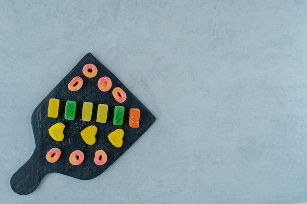 Ein schwarzes holzbrett voller bunter fruchtgummibonbons auf einer weißen oberfläche